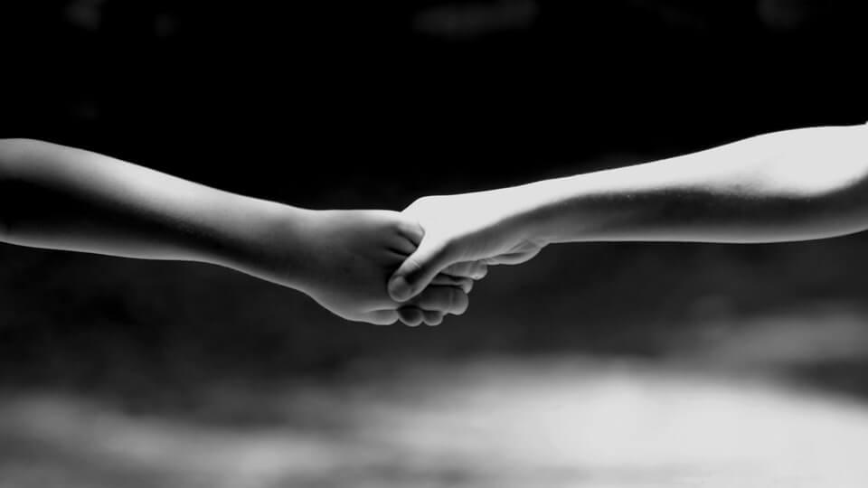 人と人の繋がりをイメージした手をつないでいるモノクロ写真